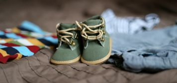 Baby shoes and baby clothes on a bed