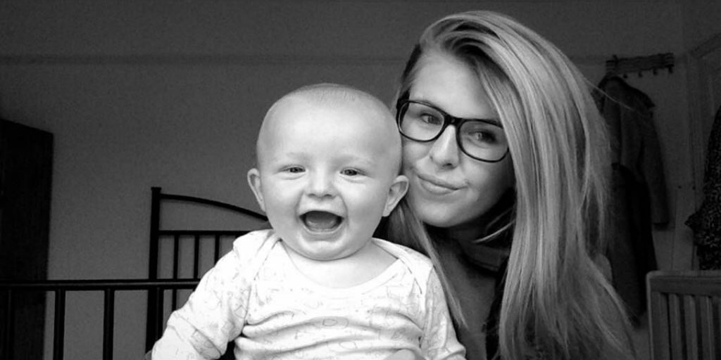 Young mum poses with her laughing baby